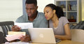 Young black couple paying bills online with laptop computer serious Stock Photography