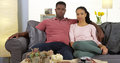 Young black couple sitting on couch looking at camera attractive Royalty Free Stock Photo
