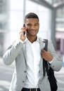 Young black man with bag talking on mobile phone Royalty Free Stock Photo
