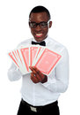 Young black man holding out deck of cards Royalty Free Stock Photos