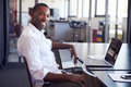 Young black man sitting at desk in office smiling to camera Royalty Free Stock Photo