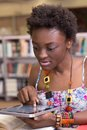 Young black student using her tablet studying working on assingment Stock Photos