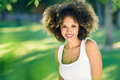 Young black woman with afro hairstyle smiling in urban park Royalty Free Stock Photo