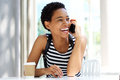 Young black woman sitting at cafe talking on mobile phone Royalty Free Stock Photo