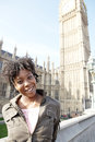 Young black woman tourist visiting big ben in london with a blue sky Royalty Free Stock Photo