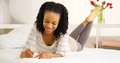 Young black woman writing in journal on bed Royalty Free Stock Photo