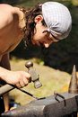 Young blacksmith hammering hot iron Stock Images