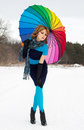 Young blond beautiful woman against wood bright scarf color umbrella winter Stock Photos