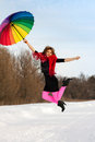 Young blond beautiful woman jumping against wood bright scarf color umbrella winter Stock Images