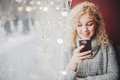 Young blond curly beautiful female smiling using a smartphone Royalty Free Stock Photo