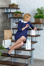 Young blond elegant woman unpacking her shopping bags on the stairs Royalty Free Stock Photography