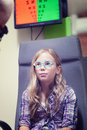 A young blond girl having an eye examination at an optometrist s clinic Stock Photography