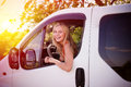 Young blond girl laughing driving white car on Royalty Free Stock Photo