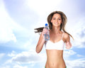 A young blond girl running with a bottle of water and sporty the image is taken outdoors on sunny sky background Royalty Free Stock Image