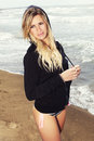 Young blonde hair girl at sea in bathing suit and sweatshirt with hood Royalty Free Stock Photo