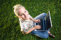 Young blond girl using laptop in sunlit park.. Stock Images