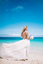 Young blond long hair bride wear a white open back wedding dress and stand on the white sand beach with a pearl. Looking to the se Royalty Free Stock Photo