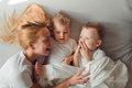 Young blond mother playing with her two sons in bed in the morning Royalty Free Stock Photo