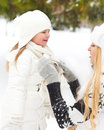 Young blond mother takes care of her daughter outd outdoors winter Royalty Free Stock Image