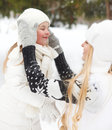 Young blond mother takes care of her daughter outdoors winter Royalty Free Stock Images