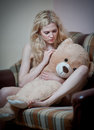 Young blond sensual woman sitting on sofa relaxing with a huge teddy bear beautiful girl comfortable clothes the Royalty Free Stock Image