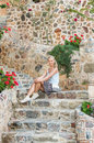 Young blond tourist woman sitting on ancient stone stairs in the Old city, Alanya, Turkey.