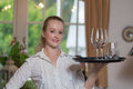 Young blond waitress in a restaurant holding tray full of glasses Stock Photos