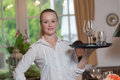 Young blond waitress in a restaurant holding tray full of glasses Royalty Free Stock Photo