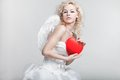 Young blond woman in angel costume holding heart Stock Photography