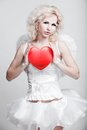 Young blond woman in angel costume holding heart Stock Photos
