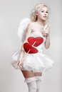 Young blond woman in angel costume holding heart arrow Royalty Free Stock Photography