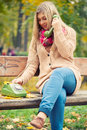 Young blond woman calling on vintage phone in autumn park Royalty Free Stock Photos