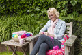 Young Blond Woman Crochets In The Garden Royalty Free Stock Photo