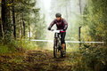 Young blond woman cyclist rides along a forest trail