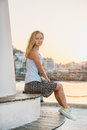 Young blond woman enjoying sunset and sitting on bench of the Alanya's Lighthouse near the water. Royalty Free Stock Photo