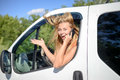 Young blond woman excited and speaking phone in portrait of exciting girl looking from car window happy smiling while talking with Royalty Free Stock Photography