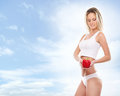 A young blond woman holding a fresh paprika and fit caucasian in white lingerie and tasty red the image is taken on blue sky Royalty Free Stock Photography