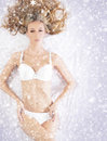 A young blond woman laying in white lingerie on snow and fit caucasian the image is taken snowy background Royalty Free Stock Image