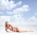 A young blond woman in lingerie relaxing on the beach and attractive caucasian light image is taken blue sky and sea background Royalty Free Stock Image