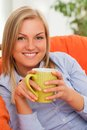Young blond woman with mug caucasian smiling in orange sofa Royalty Free Stock Photo