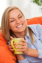 Young blond woman with mug caucasian smiling in orange sofa Royalty Free Stock Images