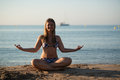 Young blond woman relaxing doing yoga sand beach sea yacht background Stock Images