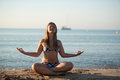 Young blond woman relaxing doing yoga sand beach sea yacht background Royalty Free Stock Photo