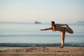 Young blond woman relaxing doing yoga sand beach sea yacht background Royalty Free Stock Photography