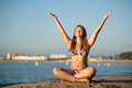 Young blond woman relaxing doing yoga sand beach sea yacht background Royalty Free Stock Image