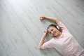 Young blond woman relaxing on the floor listening to music Royalty Free Stock Photo