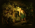Young blond woman walking into enchanted forest in dress on a mysterious path an she holding kerosene lamp Royalty Free Stock Photos