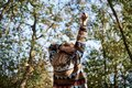 Young blond woman, wearing colorful cardigan, stretching her arms up to the sun in park in autumn. Close-up picture of girl from