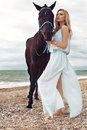 Young blond woman wears elegant dress, posing with black horse Royalty Free Stock Photo