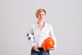 Young blonde architectress is holding architectural plans in orange safety helmet rolled isolated on white background Stock Photo